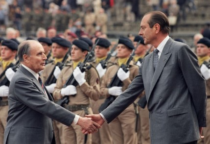 French socialist President Francois MItterrand (L) shakes hands with his neo-Gaullist Prime Minister Jacques Chirac 18 June 1987, at Mont Valerien in the Paris suburbs during a ceremony commemorating General Charles de Gaulle's appeal to resist the German occupation of France. AFP PHOTO PHILIPPE BOUCHON